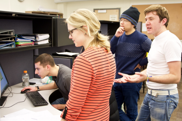 Heather Reed, center, visiting lecturer in the School of Civil and Environmental Engineering,  reviews students' projects during the Cornell Winter Session course Professional Experience in Structural Mechanics. The structural mechanics and materials master's of engineering students were working on simulating ductile fracture of large-scale structural problems via computer models.