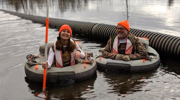 Eirini Sarri and Mike Rolband in inner tubes in a pond, smiling