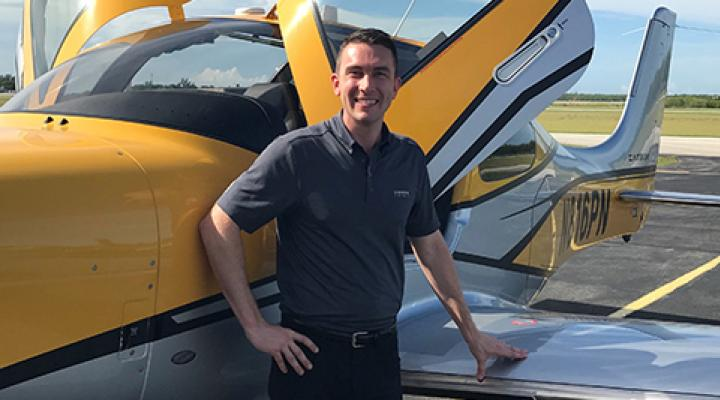 Nate Delaney standing by a Cirrus Aircraft.