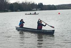 Two students paddle in a concrete canoe