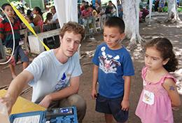 A student on location with AguaClara demonstrates technology to two children in Nicaragua