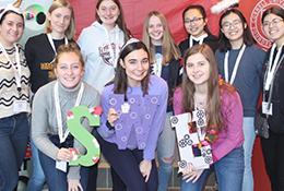 "Members of the Society of Women Engineers at Cornell stand smiling in a group with homemade giant letters ""SWE"""
