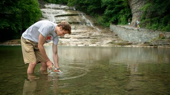 student collecting water sample