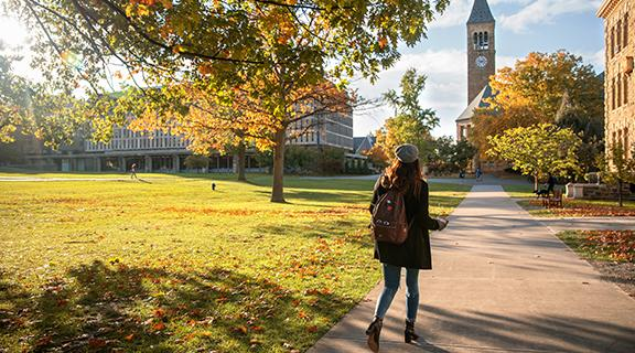A student walks through campus in fall
