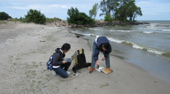 Two students on the beach with equipment