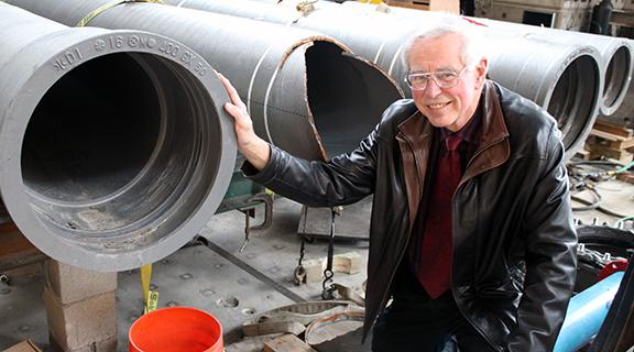 Tom O'Rourke in bovay lab in front of large pipes