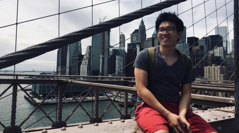 Bill Wu sitting on a bridge with a city skyline in background